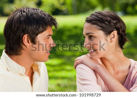 Woman smiling while looking at her friend as she has a hold of her shoulder in a park - stock photo