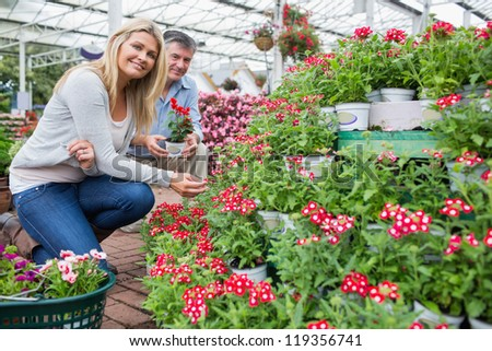 Woman smiling while looking for plants in garden ceter with man holding potted plant