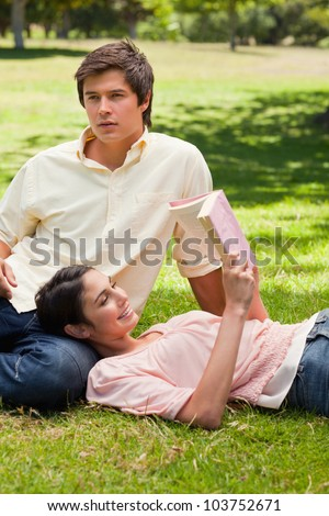 Woman smiling while she is lying against her friend's leg as she is reading a book - stock photo