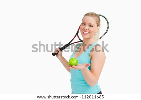 Woman smiling while showing a yellow tennis ball against white background