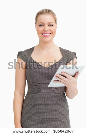 Woman smiling while using an ebook against white background - stock photo