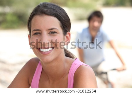 woman smiling with a man biking in background