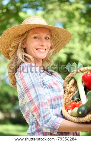 Woman smiling with a straw hat holding basket of vegetables. - stock photo