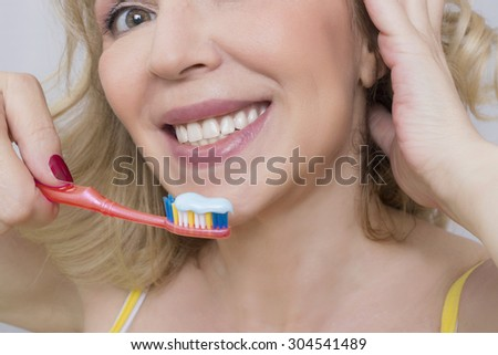 Woman smiling with a toothbrush
