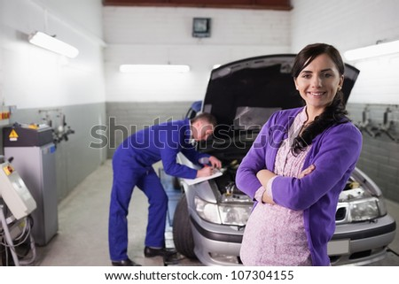 Woman smiling with arms crossed next to a mechanic in a garage