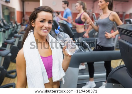 Woman smiling with bottle of water in the gym - stock photo