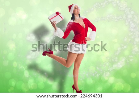 Woman smiling with christmas present against green abstract light spot design - stock photo
