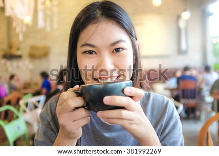 Woman smiling with coffee cup in hipster coffee shop and many people background