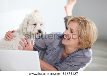 Woman smiling with dog and laptop - stock photo