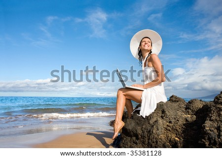 woman smiling with laptop computer on tropical beach - stock photo