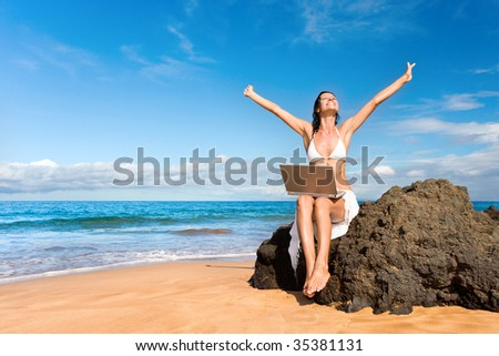 woman smiling with laptop computer on tropical beach