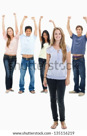 Woman smiling with people with their arms raised behind her against white background - stock photo