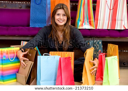 woman smiling with shopping bags in a retail store - stock photo