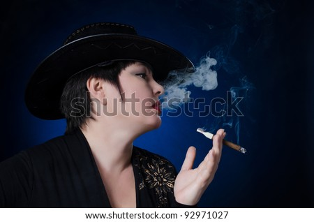Woman smokes cigar on a blue background - stock photo