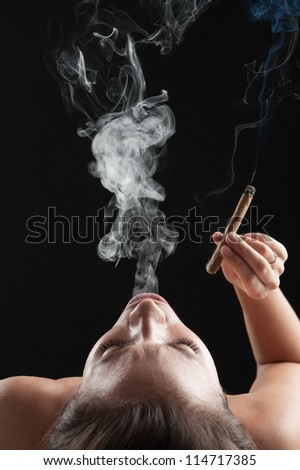 Woman smoking cigar against dark background. Studio fashion photo.