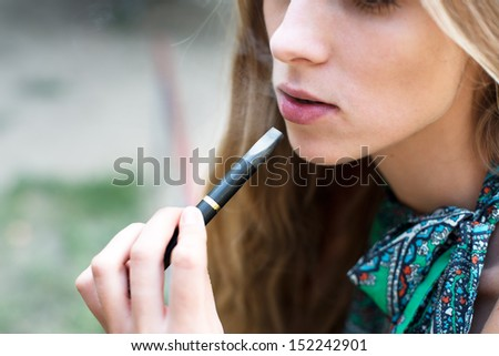 Woman smoking electronic cigarette outdoor - stock photo