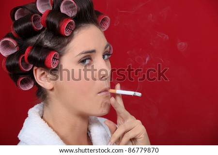 Woman smoking with her hair in rollers - stock photo