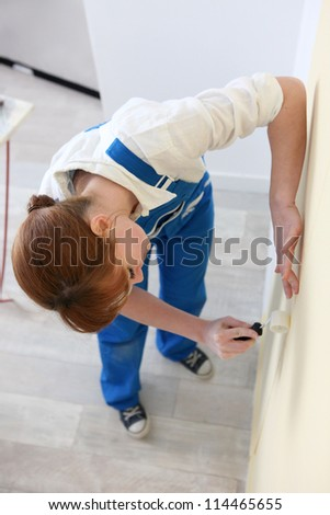 Woman smoothing a wallpaper seam - stock photo