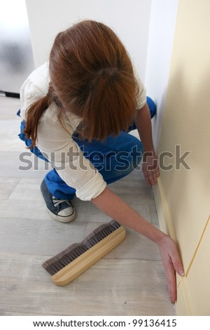 Woman smoothing down wallpaper - stock photo