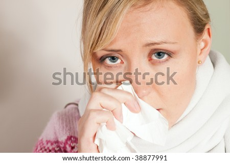 Woman sneezing, having a flu and looking feverish - stock photo