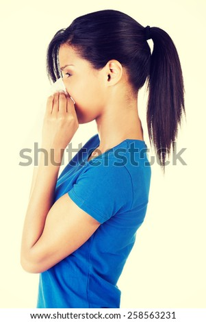 Woman sneezing in a tissue. - stock photo