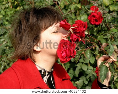 woman sniffing at a red roses