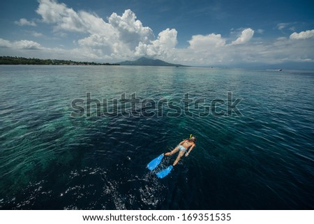 Woman snorkeling in a tropical sea by reef's drop off. Indonesia - stock photo