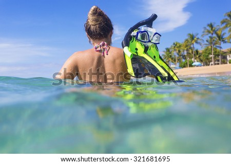Woman snorkeling in the ocean at a tropical island resort - stock photo