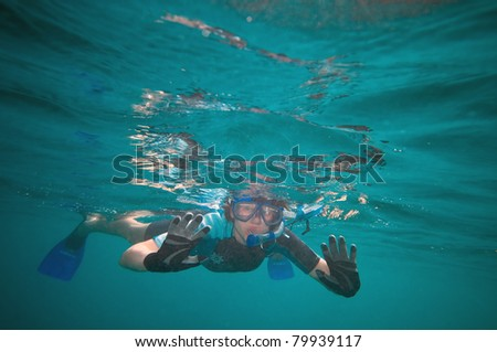 Woman snorkeling in the open ocean looking curiously at something - stock photo