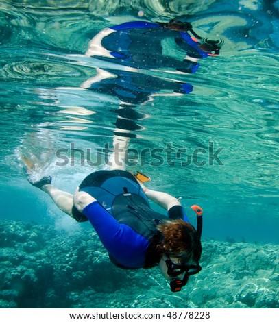 Woman snorkeling in the sea - stock photo