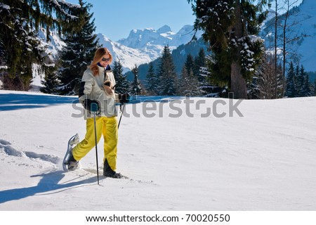 Woman snow-shoeing in the mountains - stock photo