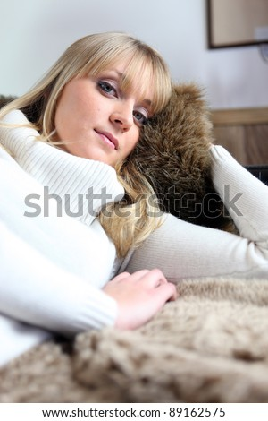 Woman snuggling up on her sofa - stock photo