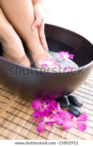 Woman soaking feet in bowl of floral scented water in spa