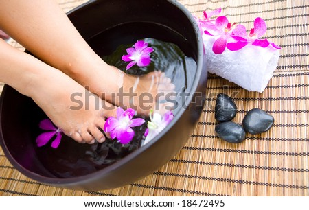 Woman soaking feet in bowl of floral scented water in spa - stock photo