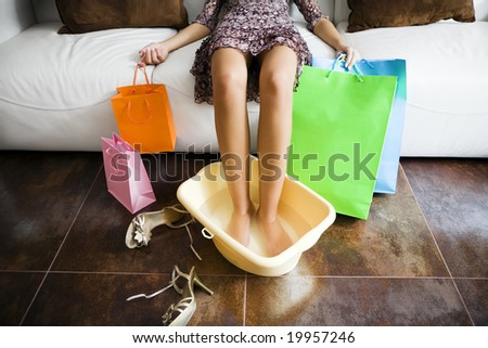 Woman soaking feet in water after long day shopping - stock photo