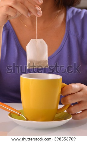 Woman soaking tea bag on yellow cup, preparing hot tea.Dipping teabag on cup. - stock photo