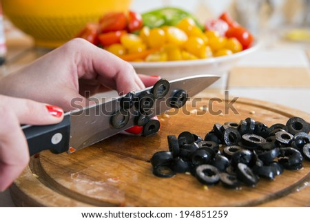 Woman soft fingers cut black olives to slices - stock photo