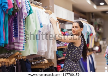 Woman sorting clothes on rail in clothes shop