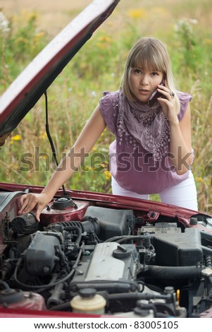 woman speaking by mobile near  her broken car - stock photo
