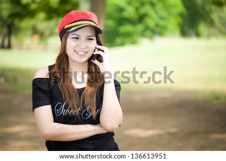 Woman speaking on mobile phone at green park - stock photo