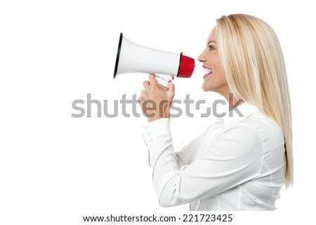 Woman speaking over a megaphone making a public announcement - stock photo