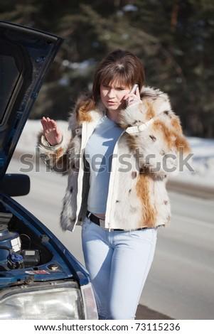 Woman speaking speaking by mobile near  her broken car - stock photo