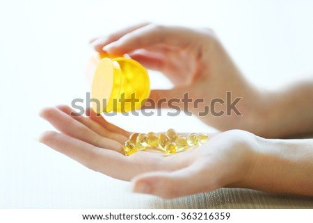 Woman spills yellow medical capsules  to her hand, close up