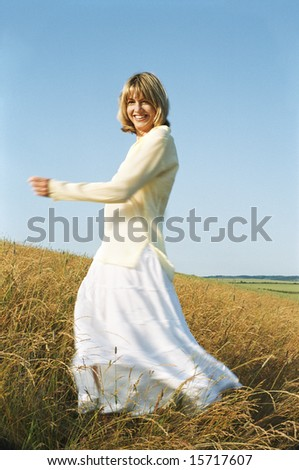 Woman spinning outdoors smiling - stock photo
