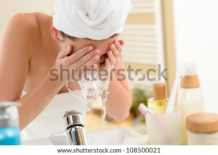 Woman splashing face with water above bathroom sink