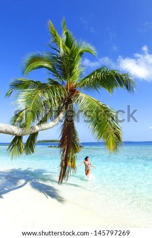 Woman splashing in sea near beautiful beach with palm - stock photo