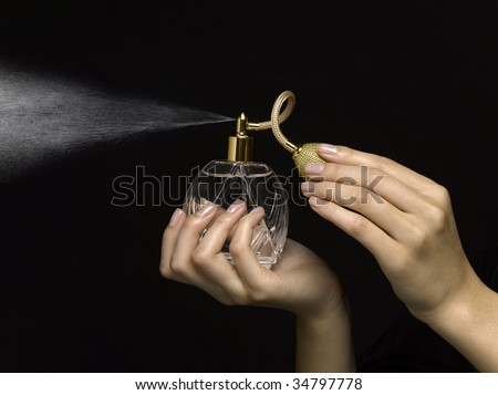 Woman spraying perfume with perfume atomizer, close-up of hands - stock photo