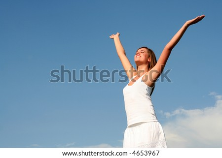 Woman spreading arms to sky - stock photo