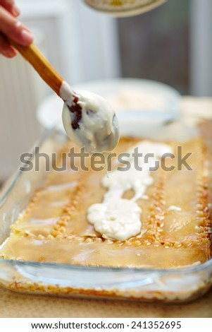 Woman spreading bechamel sauce on lasagna pasta in a tray - stock photo