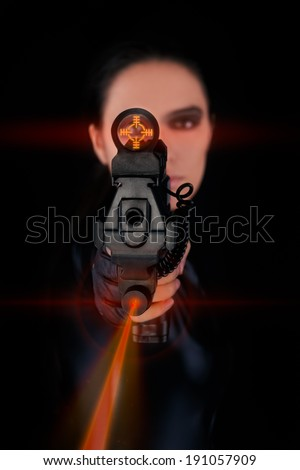 Woman Spy Aiming Gun with Laser Sights - Woman in a black leather suit pointing a gun with laser sights at the camera  - stock photo